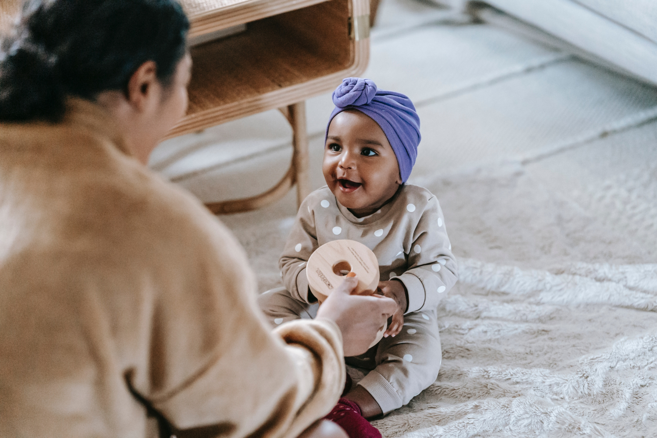 A baby playing with an early child development and care worker