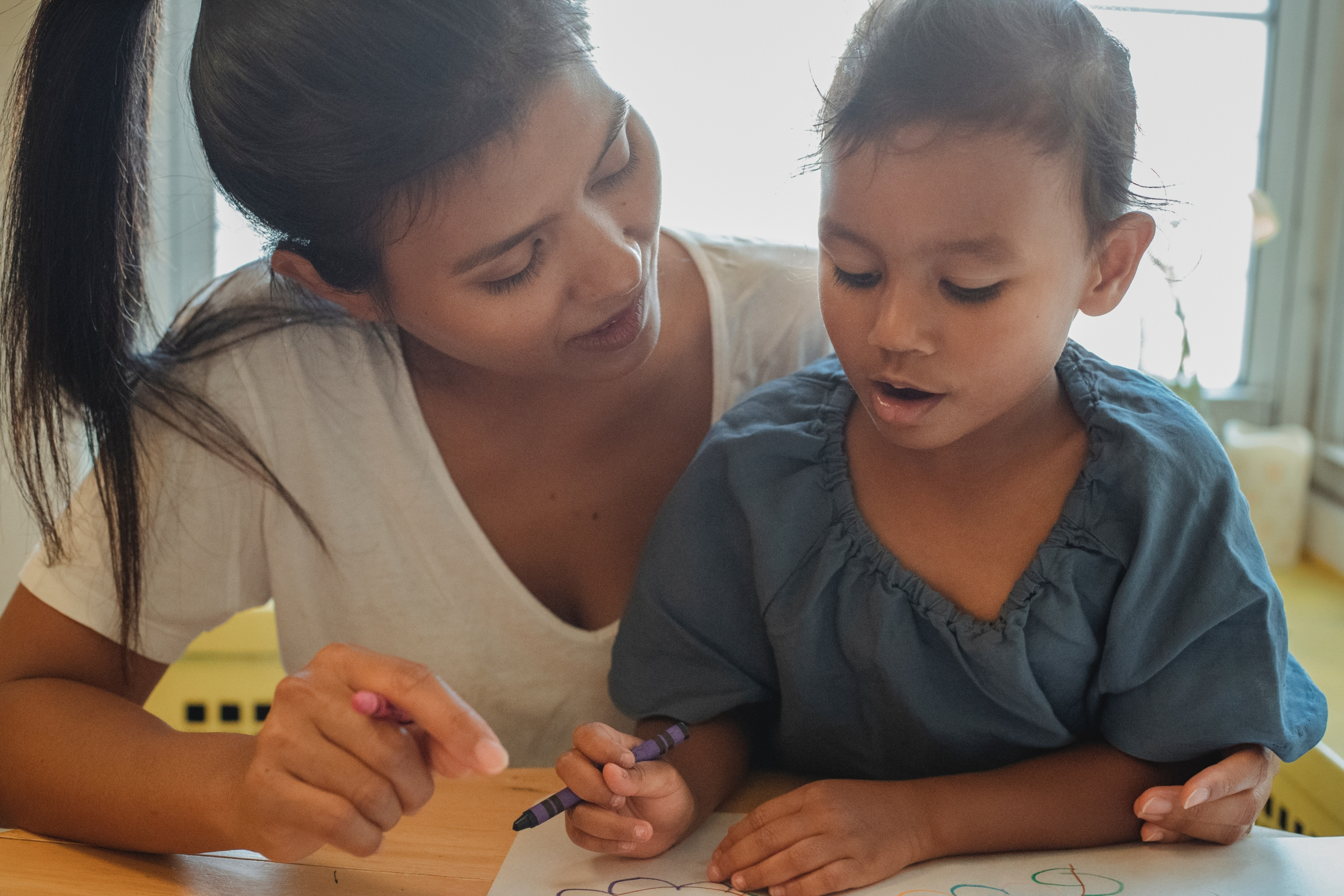 Woman and child coloring, making use of child care resources